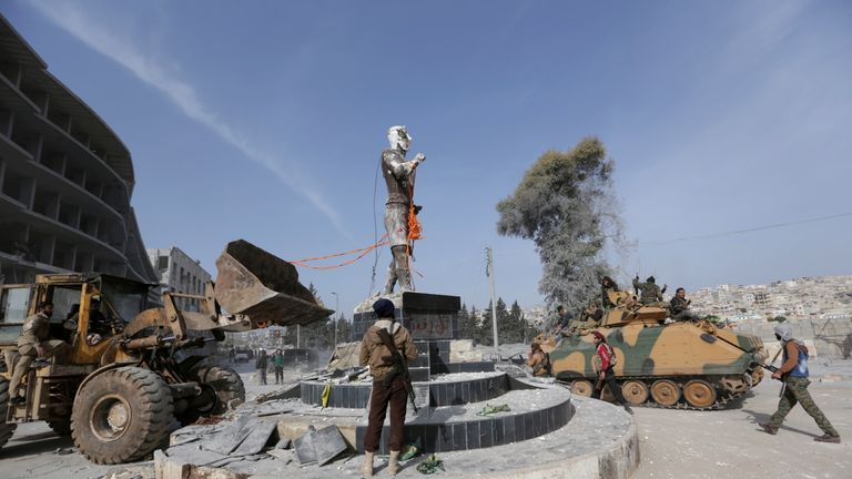 Turkish-backed Free Syrian Army fighters pull down a Kurdish statue in the centre of Afrin