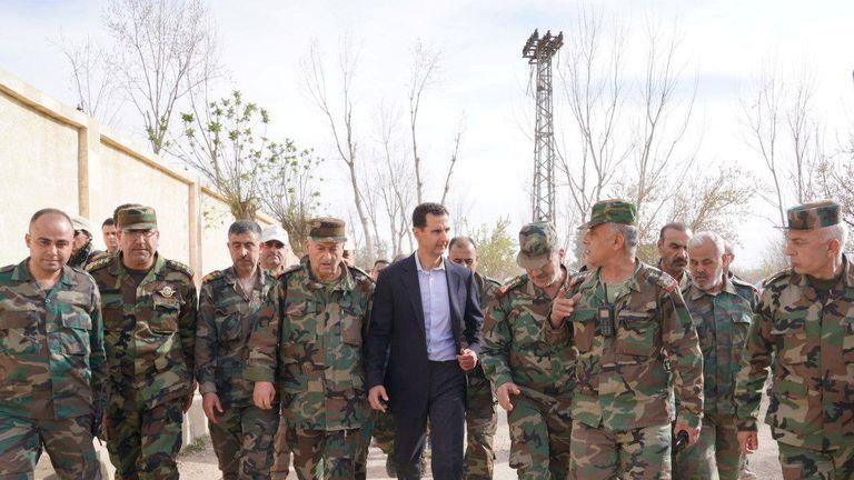 Syrian President Bashar al-Assad walks with Syrian army soldiers in eastern Ghouta