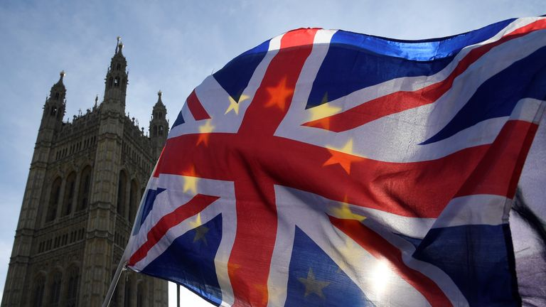 Anti-Brexit demonstrators wave EU and Union flags outside the Houses of Parliament