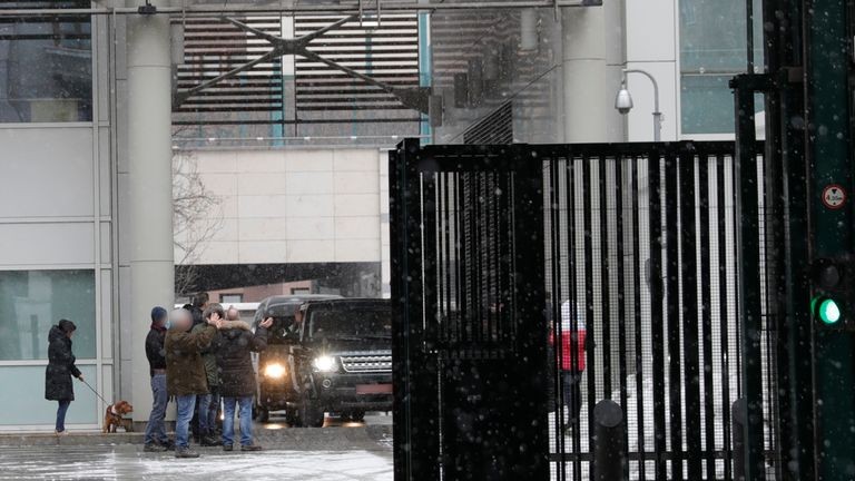 Members of the British embassy staff applaud as a convoy of vehicles leaves its compound in Moscow