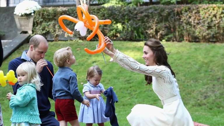 George and Charlotte play with balloon animals in Canada