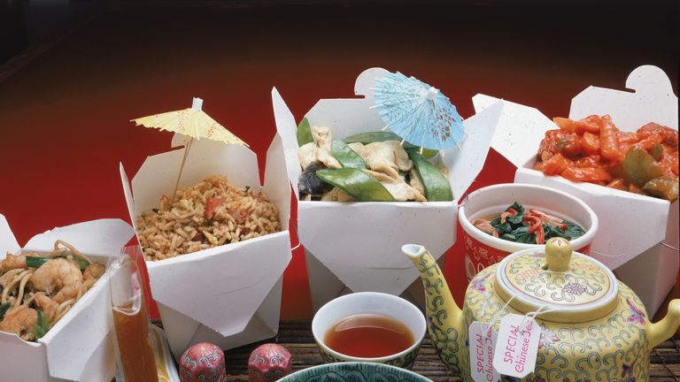 A display of Chinese take-out food and appropriate serving and eating items includes a Chinese-theme patterned bowl, saucer, and soup spoon, condiments, a teapot and tea, and four take-out containers containing (left to right) shrimp lo mein, pork-fried rice, sliced chicken and snow peas, and sweet and sour chicken, 1970s