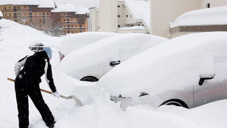A woman removes the snow from her car in Saint-Chaffrey, France
