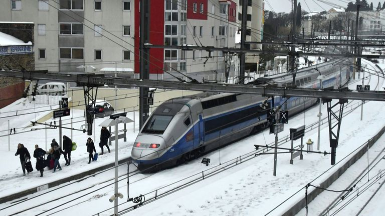 Passengers walk out a TGV train blocked by snow in Montpellier in the south of France