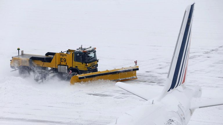 A snow plough removes snow next to Air France aircraft during a temporary closure at Cointrin airport in Geneva, Switzerland