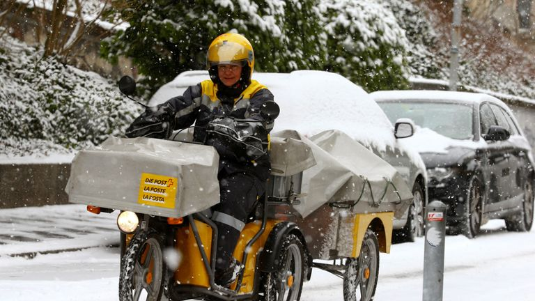 A mailwoman of Swiss mail operator Schweizerische Post rides her electro-powered trike on a snow-covered street in Zurich, Switzerland