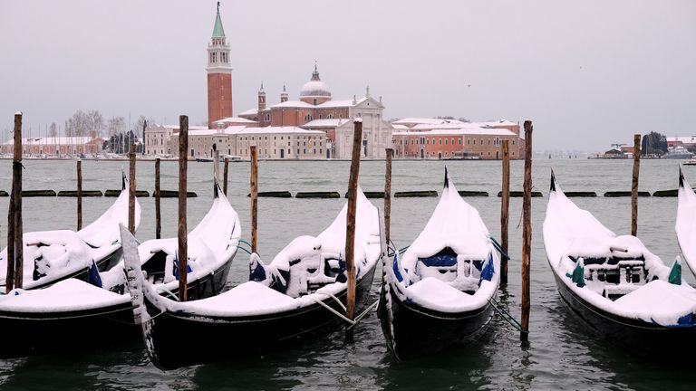 Snow covered gondolas near St. Mark's square in Venice lagoon