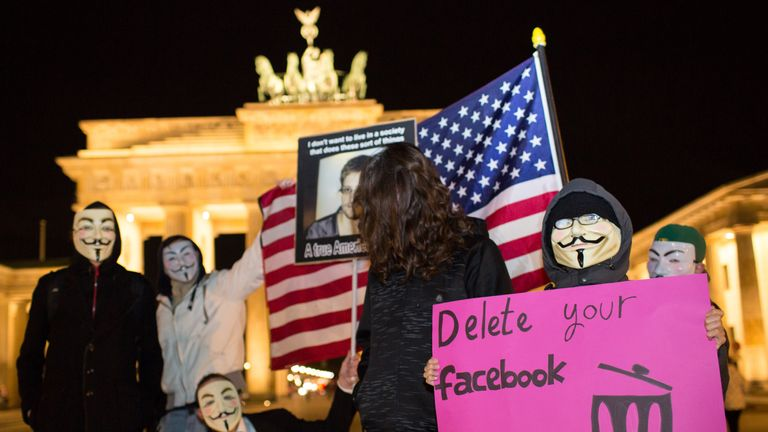 Supporters of the Anonymous group wearing Guy Fawkes masks holds up a placard featuring a photo of US intelligence leaker Edward Snowden and a poster reading 'Delete your facebook' during a rally in front of Berlin's landmark Brandenburg Gate on November 5, 2013. The 'One million masks' protests organized by the Anonymous group are taking place on Guy Fawkes Day all over the world. AFP PHOTO / DPA / FLORIAN SCHUH +++ GERMANY OUT (Photo credit should read FLORIAN SCHUH/AFP/Getty Images)