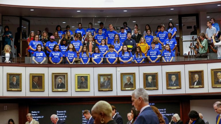 Students and their chaperones from Marjory Stoneman Douglas High School, wearing blue t-shirts, stand in the gallery above the Florida Senate as the Senate holds a moment of silence to honour the victims of the mass shooting on the school's campus, in Tallahassee, Florida, U.S., February 21, 2018