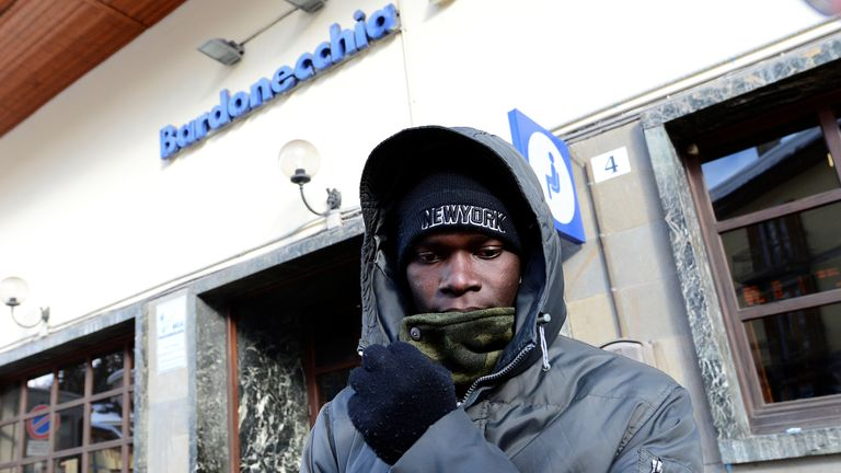 """A migrant stands outside the Bardonecchia train station in Italy which was """"raided"""" by French border officers"""