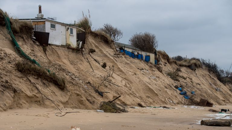 Dogs run along Hemsby beach in front of houses that have been evacuated after high winds and waves eroded the dunes on which they sit in Norfolk