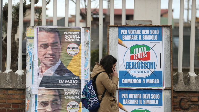A woman passes electoral posters in Naples ahead of the polls opening