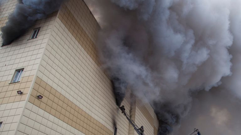 Smoke billows from the centre as firefighters battle to extinguish the flames