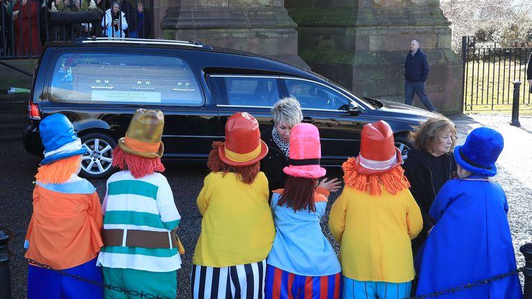 Children dressed as diddymen watch Ken Dodd's funeral cortege