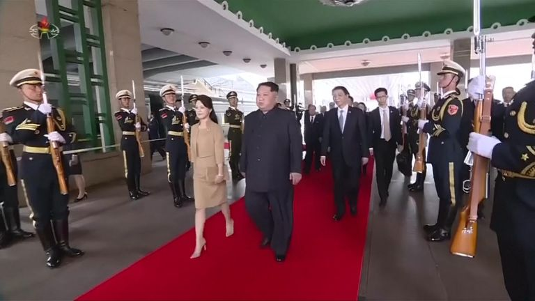 Kim Jong Un and his wife walked up the red carpet in Beijing Train Station as Xi Jinping and his party members followed