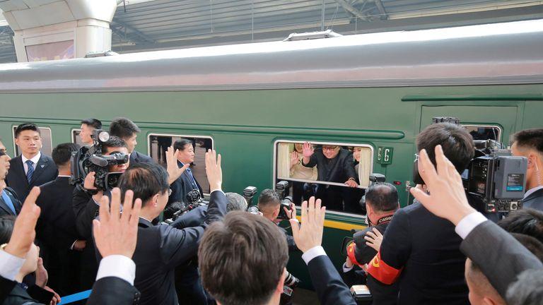 Kim Jong Un and his wife Ri Sol Ju waving at Chinese media from his diplomatic train