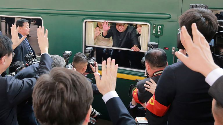 Kim Jong Un waving from his train as it prepares to depart from Beijing railway station