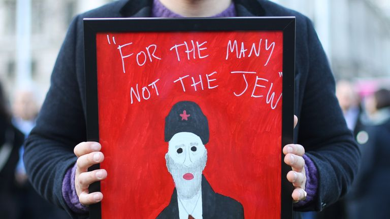 "A demonstrator holding a painting saying ""For the many not the Jew"""
