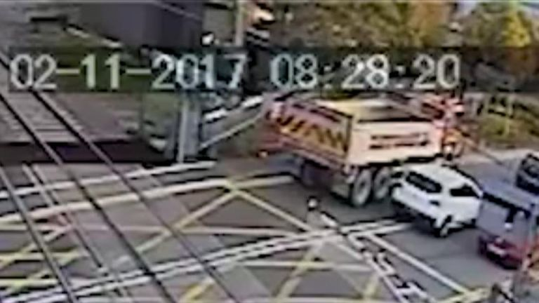 Level crossing damaged as it lowers down onto a stationary truck