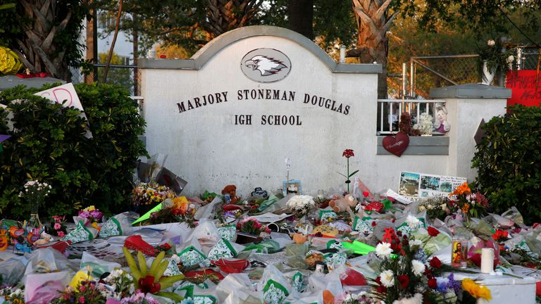 Flowers, candles and mementos sit outside one of the makeshift memorials at Marjory Stoneman Douglas High School in Parkland, Florida on February 27, 2018