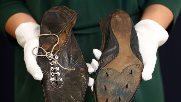 A Christie's employee holds running shoes worn by Sir Roger Bannister when he became the first man in history to run one mile in under four minutes