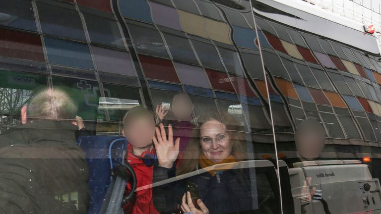 People wave out of the window after their van bearing diplomatic plates left the Russian Embassy in London