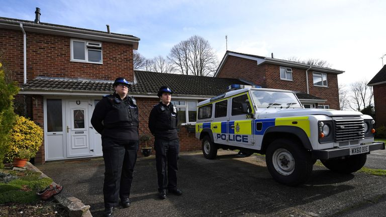 British Police Community Support Officers stand on duty outside a residential property in Salisbury