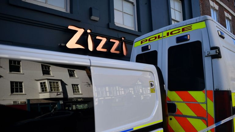 Police vehicles on the pavement inside the cordon outside the restaurant Zizzi