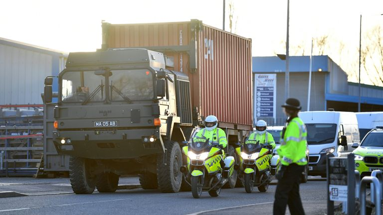 Police motorcycle out-riders escort a British army truck, carrying a freight container laden with the car of Sergei Skripal