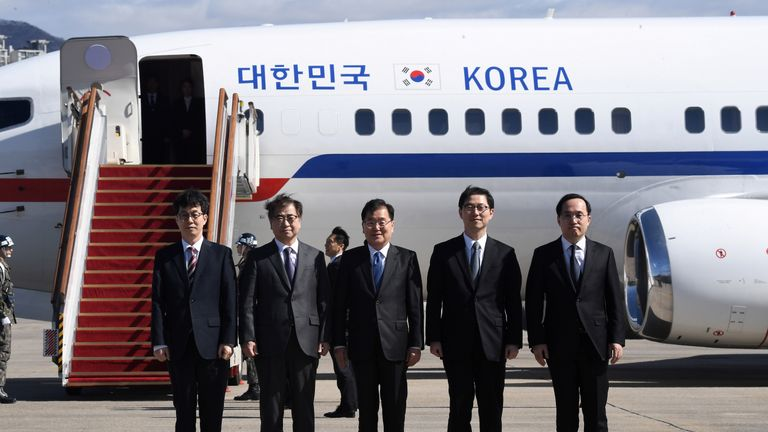 The South Korean delegation pose before boarding an aircraft for Pyongyang