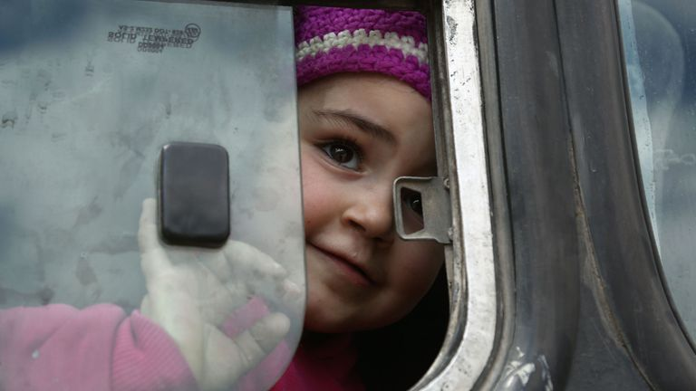 A Syrian girl opens the bus window after being evacuated from Eastern Ghouta on Sunday
