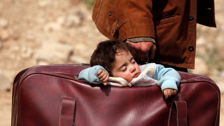 A child sleeps in a bag in the village of Beit Sawa, eastern Ghouta, Syria