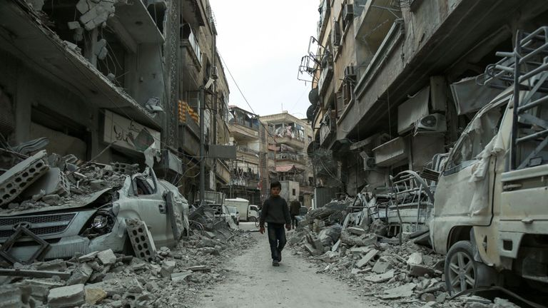A picture taken on March 8, 2018 shows a Syrian child walking down a street past rubble from destroyed buildings, in the rebel-held town of Douma in the Eastern Ghouta enclave on the outskirts of Damascus