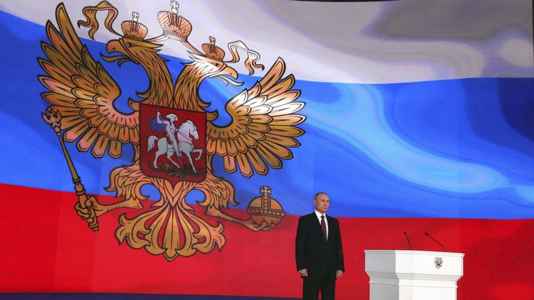 Russian President Vladimir Putin stands on the stage as he addresses the Federal Assembly