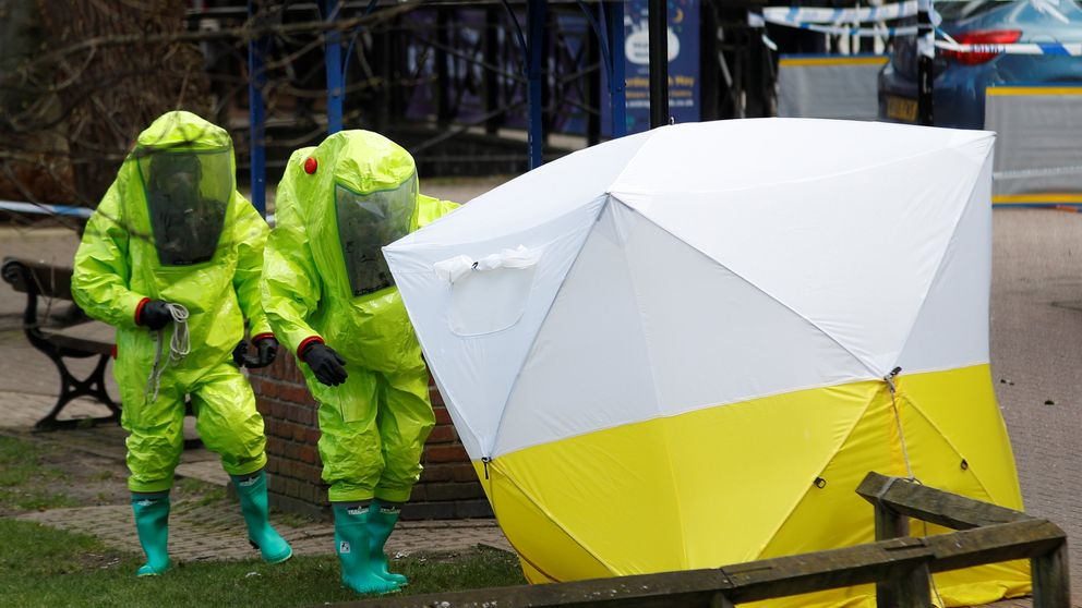 The forensic tent, covering the bench where Sergei Skripal and his daughter Yulia were found, is repositioned by officials in protective suits