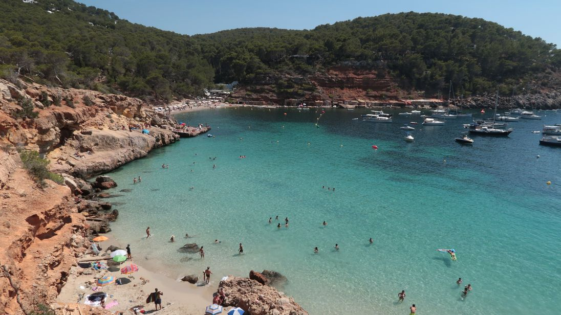 Bathers relax at Cala Saladeta beach on the island of Ibiza