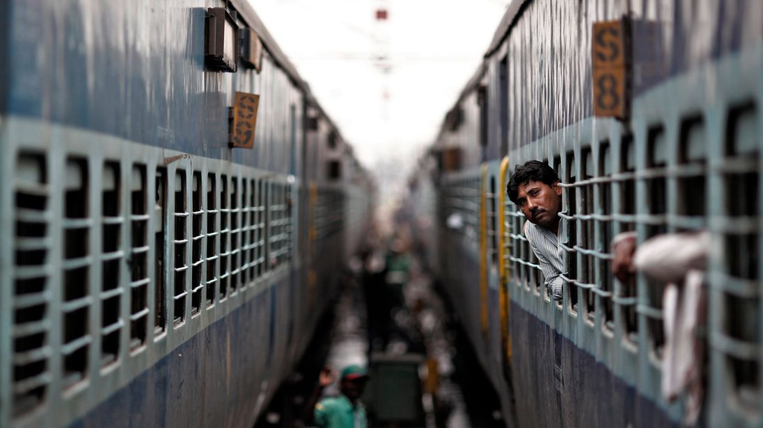 A passenger looks through the window of a train at a railway station in New Delhi