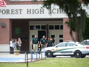 Police officers stand outside Forest High School after a school shooting where one person was hurt