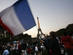 A France's fan waves a French flag on the Champs-de-Mars near the Eiffel Tower, center Paris, during the rugby union World Cup 2007 semi final match England vs. France at the Stade de France in Saint-Denis, northern Paris, 13 October 2007. AFP PHOTO GUILLAUME BAPTISTE (Photo credit should read GUILLAUME BAPTISTE/AFP/Getty Images)