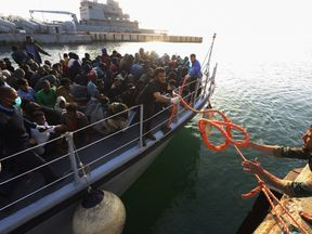 Illegal migrants of different African nationalities arrive at a naval base in the capital Tripoli