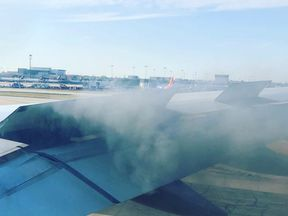 Smoke can be seen billowing from an engine of a Delta Air Lines plane which caught fire at Atlanta International Airport