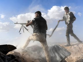 TOPSHOT-SYRIA-CONFLICT TOPSHOT - A member of the Syrian pro-regime forces fires a machine gun as a comrade holds his feeding ammunition belt, during the advance towards rebel-held positions west of Aleppo, near Abu al-Zuhur military airport in the Idlib province countryside, on November 11, 2017