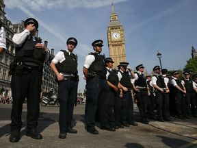 Police stand guard as protesters gather in Parliament Square after marching through central London on June 21, 2017, during an anti-government protest to coincide with the State Opening of Parliament and following the deadly fire at Grenfell Tower.