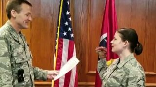 Master Sergeant Robin Brown uses a dinosaur puppet during her enlistment ceremony