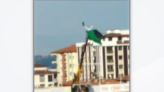 Football fan on top of a crane in Turkey