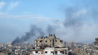 Smoke rises from one of the buildings in the city of Homs, Syria March 11, 2013