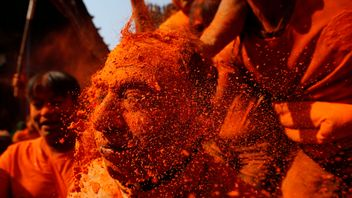 "A devotee gets his face smeared with vermillion powder during ""Sindoor Jatra"" vermillion powder festival at Thimi, in Bhaktapur, Nepal"