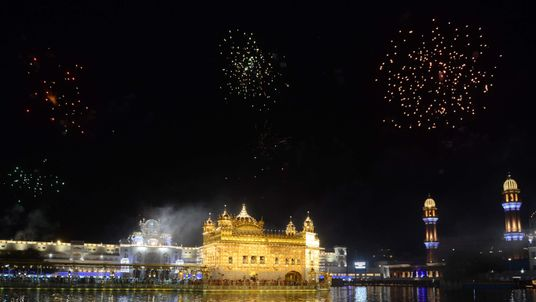 Indian Sikh devotees watch fireworks for the Baisakhi festival, which marks the new year for the Sikh community, at the Golden Temple in Amritsar on April 14, 2018. / AFP PHOTO / NARINDER NANU (Photo credit should read NARINDER NANU/AFP/Getty Images)