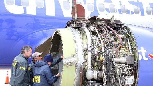 Investigators examine the damage to the plane's engine