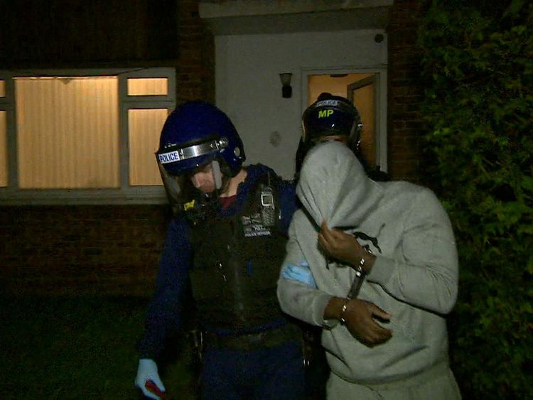 A suspect arrested during the raids is led away